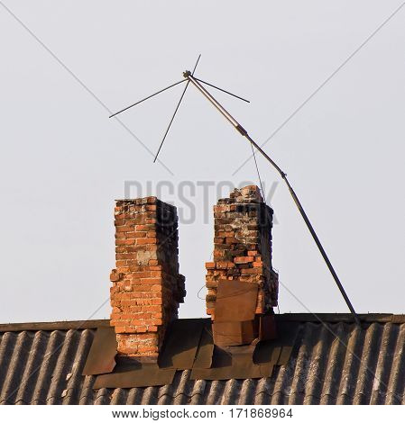 The TV antenna and the old brick chimneys on the roof