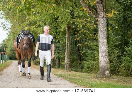 Adult Man With His Horse on horse ranch.