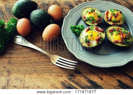 Avocado Egg Boats with bacon on wooden table. Top view.