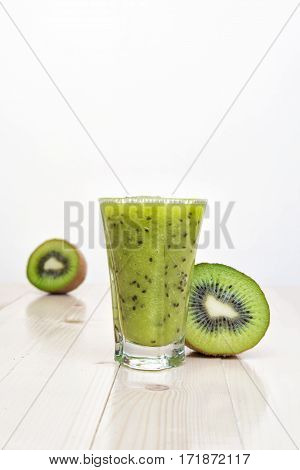 Kiwi smoothie on white wooden table and sliced fresh kiwi around