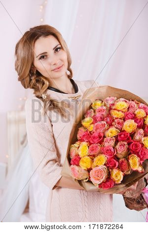 Beautiful smiling girl with bouquet of red and yellow roses.