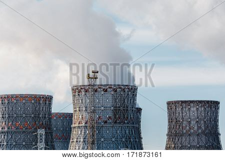 Factory pipes or Cooling towers of nuclear power plant with steam. Environmental pollution concept