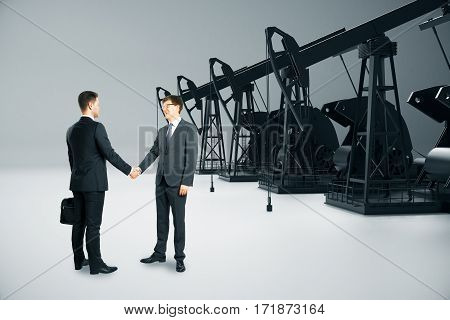 Businessmen shaking hands on light background with oil derricks. Deal concept. 3D Rendering