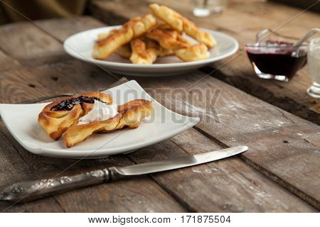 Homemade fritter with berry syrup on wooden background. Sweet breakfast for children that everyone would like.