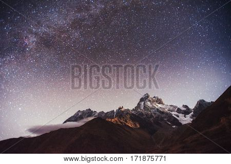 Fantastic starry sky. Autumn landscape and snow-capped peaks. Main Caucasian Ridge. Mountain View from Mount Ushba Meyer, Georgia. Europe