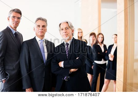 business team posing for a group shot, with men in front and women in the background. concept shot illustrating how men have an easier time advancing their career.