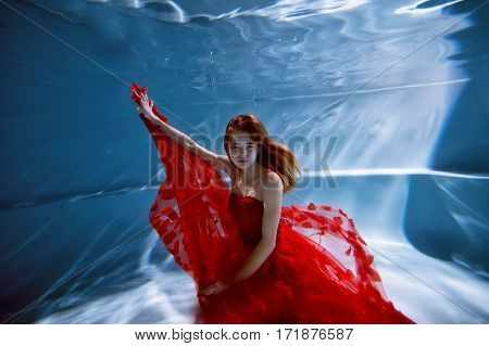 Underwater in the pool with the purest water. Beautiful girl in a scarlet dress and flowing hair.