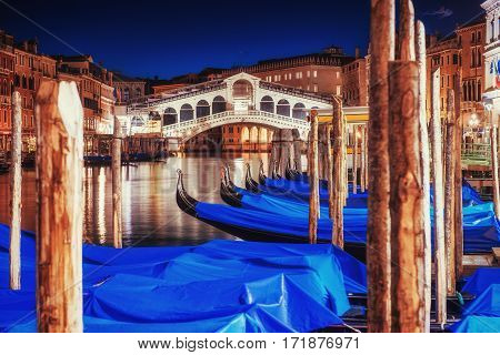 City landscape. Rialto Bridge in Venice at night. Green water with gondolas boats and colorful facades of old medieval houses in Venice. Many tourists who visit beauty all year round. Italy. Europe
