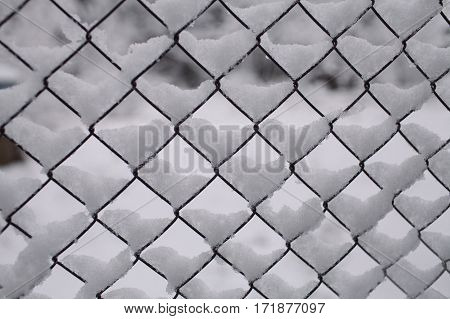 Fence background. Metallic net with snow. Metal fence in winter covered with snow. Wire fence closeup. Texture and background for designers. Wire fence covered by ice and snow.