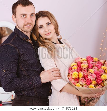Beautiful smiling woman and man studio portrait with rose bouquet.