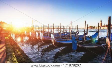 Fantastic views of the gondola at sunset, moored on San Marco square with San Giorgio di Maggiore church in the background - Venice, Italy, Europe
