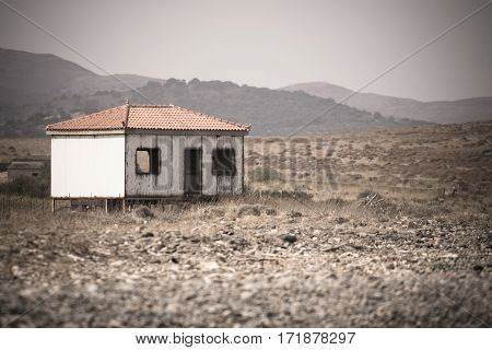 Abandoned and unused wooden house on a deserted beach.