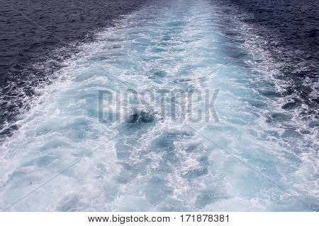 The tail of the ship leaves a trail in the blue sea foamy water after motorboat seaside photo for background. Marine backdrop image. Summer travel by boat. Cruise liner concept picture