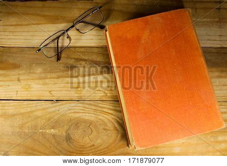 Close old book with glasses on the wooden background