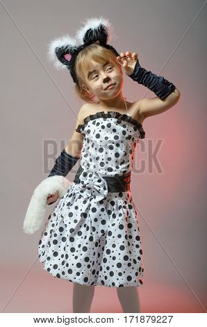 Attractive Little Girl Dressed As A Cat On A Gray Background.