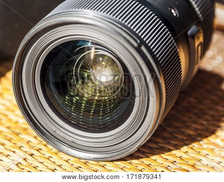 Black professional photography camera zoom lens with lot of reflections.