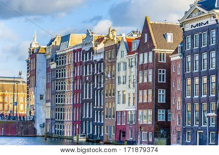 Narrow old housing buildings in Amsterdam Netherlands with reflection in a water canal.