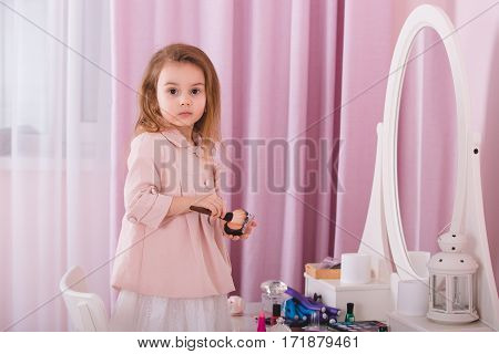Cute little girl in her mother's room playing with cosmetics