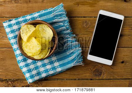 Potato Chips In A Bowl On A Wooden Table And A Smartphone.