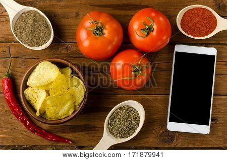 Potato Chips In A Bowl On A Wooden Table, Tomatoes And Smartphone.