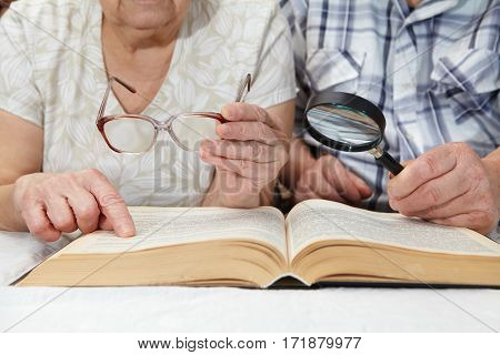 An Elderly Couple Reading A Book