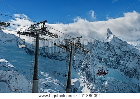 Skiers and snowboarders lift to the Ski Resort high in the winter snow mountains at chair cable car.