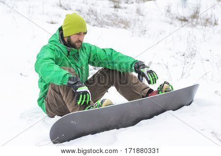Man Snowboarder Sitting In The Snow.