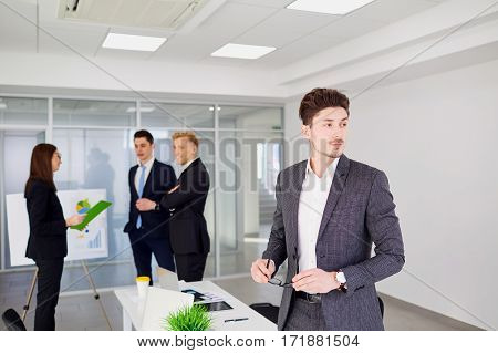 Businessman with glasses in hand looking stand on  background of business team the office.