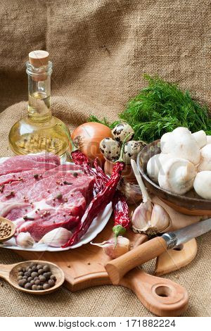 Uncooked meat : raw fresh beef pork ready to cooking with garlic onions parsley dillmushroomsquail eggsseasonings salt coriander and red hot pepper onr wood background. Raw meat with condiments.