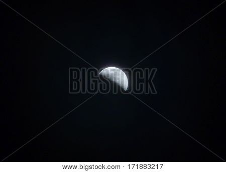 Photo of a half moon partially covered by a fog