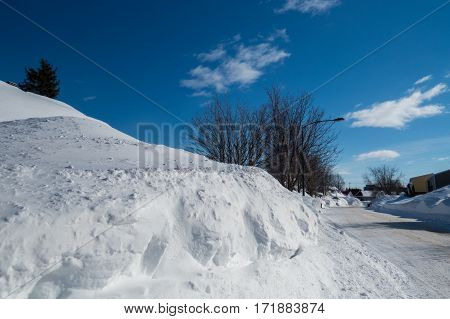Huge snowbank plowed from the street after many winter storms taken during a beautiful winter day. Levis, Quebec, Canada.