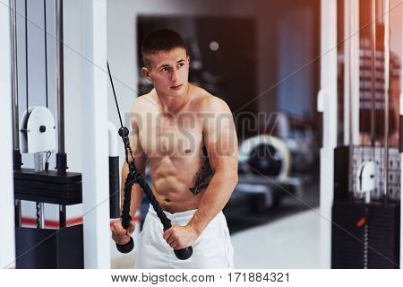 Portrait of fitness strength training workout bodybuilding concept background. Spandex nice man doing exercise at the gym with a naked torso.