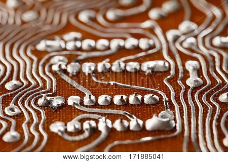 Electronic component vintage design. Brown circuit board and soldering traces macro view. Shallow depth of field photo
