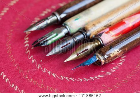 Fountain pen set. Calligraphy handwriting accessories, vintage colorful artist pens, textured pink paper background. macro view, shallow dept of field, soft focus photo