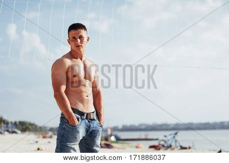 muscular male model with perfect body posing in blue jeans.