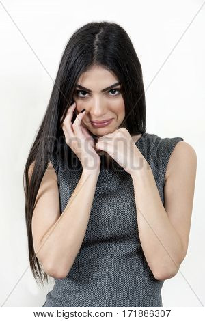Business woman has her hands on her face and looking at the camera.