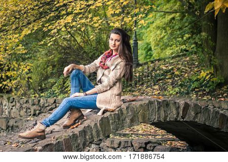 girl sitting on a stone bridge in the Park