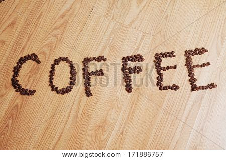 Coffee phrase spelled out of roasted coffee beans on wood background
