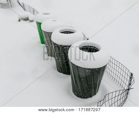 Trash and various recycling receptacles under heavy snow.