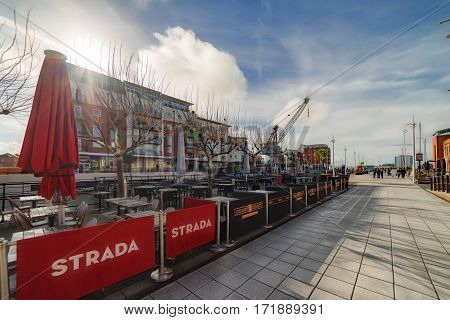 Portsmouth, UK. 16th February 2017. A sunny day at Gunwharf Quays retail and leisure facility in Portsmouth with a few people walking along the promenade.