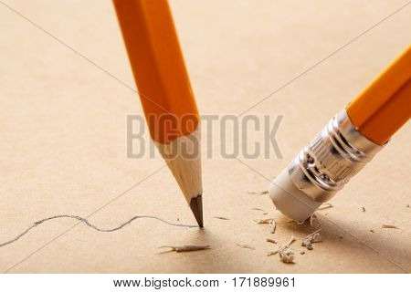 pencil draws a straight line on brown paper and pencil rubber eraser removing stripe. Business Breaking concept. Education. Art. Office supplies.
