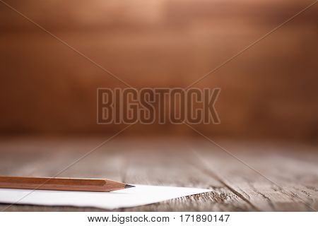 Wooden Desk Table, White Clipboard with Blank Paper. Copy space for text or Image. Natural material. White paper and brown pencil. Sharpen. Brown desk. Writing, drawing and painting.