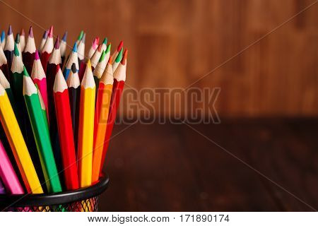 different pencils on the brown wooden table background. Colorful pencils. School and education. Drawing and painting. NAtural materials. Brown background. Pencils in the clerical glass.
