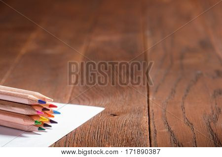 Blank paper and colorful pencils on the wooden table. Hill with a pencil. Brown background. Scholl and education. Art and design. PAinting and drawing.