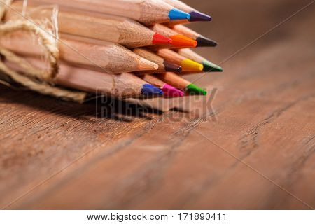 background of bunch of pencil related decorative rope on wood table. Brown background. Colorful pencils. Natural materials. Painting and drawing. Art. Education. Desig.