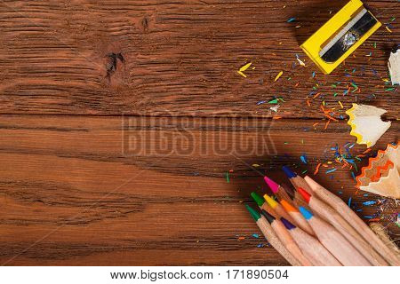 Colorful Pencils with sharpener and shawings on the wood table. Brown background. Yellow sharpen. Creative idea and concept. Art and design. School and education. Painting and drawing.