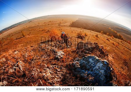 Wide angle view of cyclist standing with mountain bike on trail at sunset. Fisheye. Hill and rocks. Landscape with blue sky and sunset. Travel in the countryside.