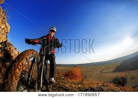 low angle view of cyclist riding mountain bike on rocky trail at sunrise. Wide angle and fisheye. Detaik of the bicycle. Wheel. Cyclist in the helmet and sunglasses. Beautiful landscape with hill, rocks and blue sky.