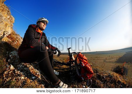 Mountain biker looking at view on bike trail in spring landscape. Male rider resting on cycling trip in nature. Sport fitness, motivation and inspiration in beautiful inspirational landscape. Cyclist in the helmet and sunglasses, with red backpack.