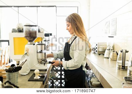 Female Barista Grinding Some Coffee
